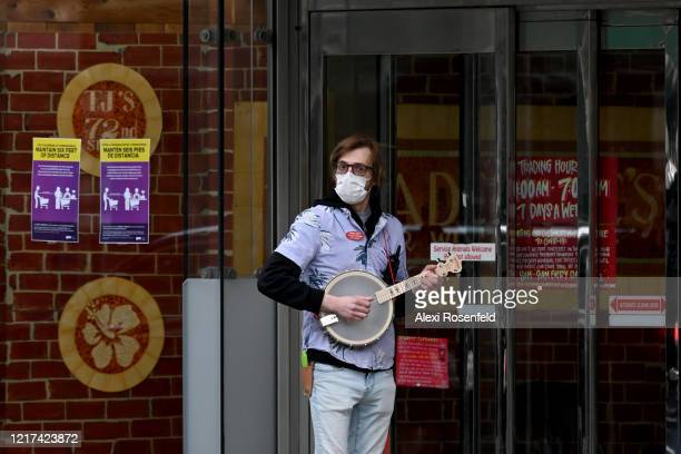 Trader Joes employee plays a banjo while people wait in line in front of the 72nd Street Trader Joe's location amid the coronavirus pandemic on April...