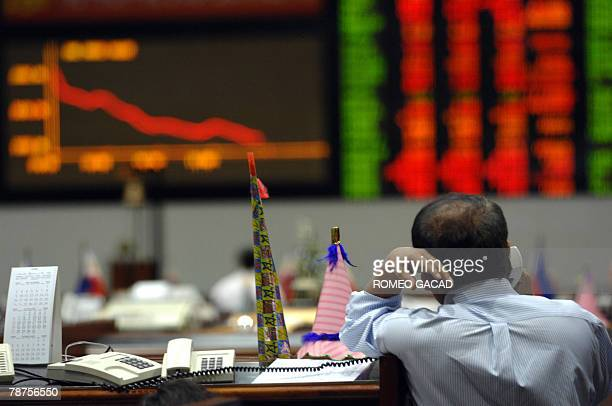A trader leans on a divider with a New Years cardboard trumpet as he looks at the dislay board of the Philippine Stock Exchange in Manila 03 January...