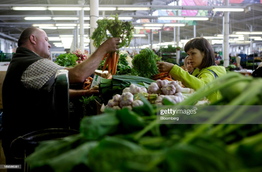 A trader, left, offers fresh carrots to a customer at a vegetable stall in Holesovicka market hall in Prague, Czech Republic, on Monday, May 27, 2013. Czech policy makers are in uncharted territory as they debate whether the first koruna sales in a decade are needed to meet their inflation target as the economy has shrunk for five quarters, the longest contraction since at least 1996. Photographer: Martin Divisek/Bloomberg via Getty Images