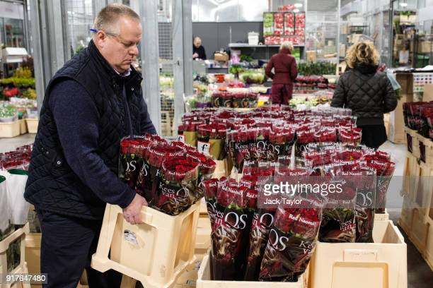 A trader lifts a box of roses at New Covent Garden Flower Market ahead of Valentine's Day on February 13 2018 in London England New Covent Garden...