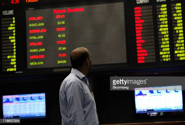 A trader looks at financial data screens in the trading hall of the Karachi Stock Exchange in Karachi Pakistan on Thursday June 16 2011 Karachi Stock...