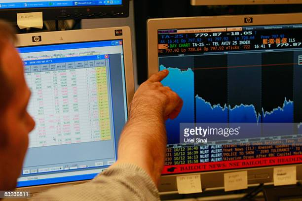 A trader looks points to his monitor as he works in a dealing room in Tel Aviv on October 12 2008 in Tel Aviv Israel Israeli shares plunged by over 8...