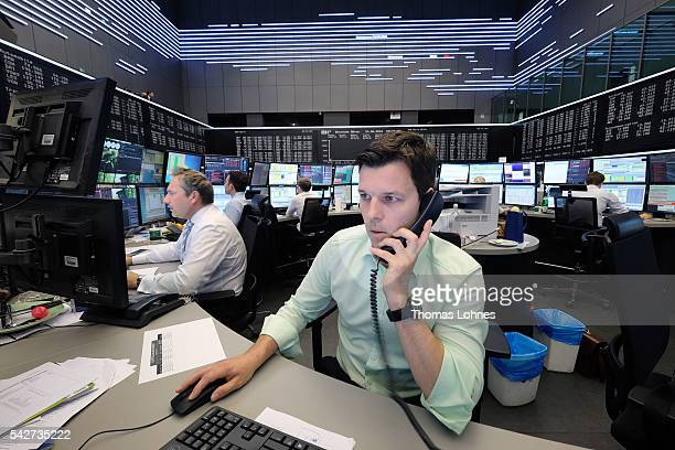 A trader looks to his computer screens whilst working at the Frankfurt Stock exchange the day after a majority of the British public voted for...