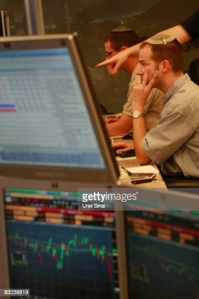 A trader looks worried as he works in a dealing room in Tel Aviv on October 12 2008 in Tel Aviv Israel Israeli shares plunged by over 8 percent on...