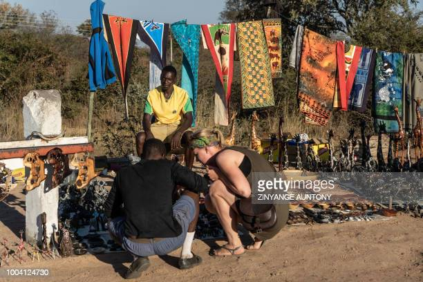 A trader manning a curio stall assist a tourist to choose souvenirs on June 29 2018 in the resort town of Victoria Falls After nearly two decades in...