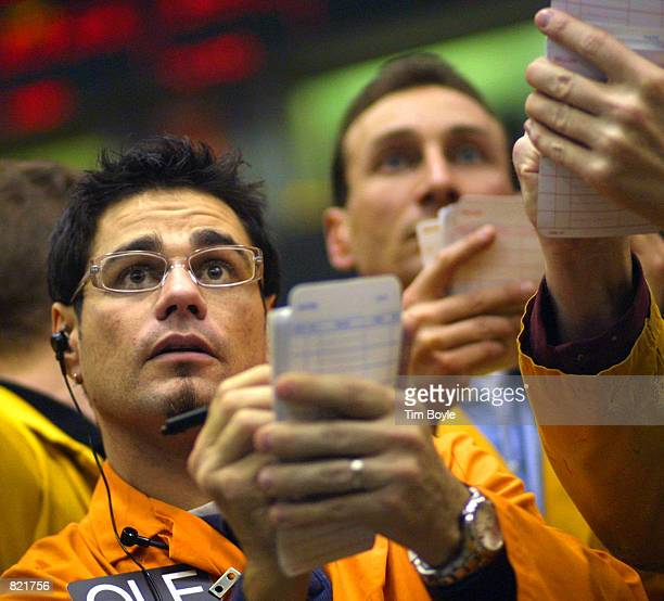 Trader Michael A Palmer left looks at prices as he writes down a trade on a trading card in the Eurodollar Futures pit of the Chicago Mercantile...
