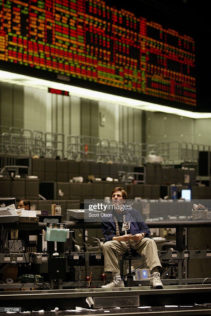 Trader Michael Cousin relaxes following the close of the Dow Jones Industrial Average stock index futures pit at the Chicago Board of Trade June 12, 2003 in Chicago, Illinois. The Dow cash index closed at 9,196.44, the highest close in over 11 months.