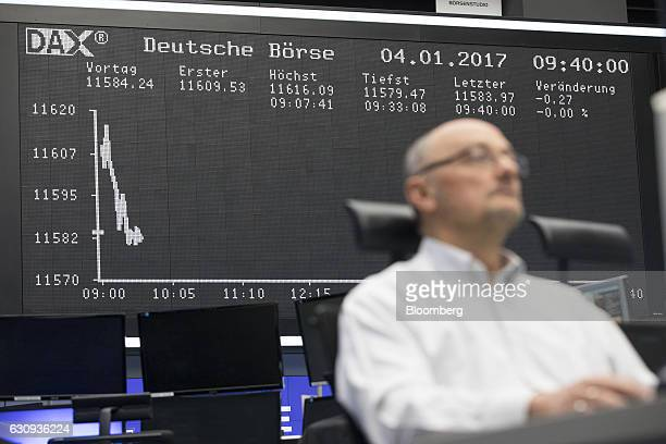 A trader monitors financial data as the DAX Index curve is displayed inside the Frankfurt Stock Exchange in Frankfurt Germany on Wednesday Jan 4 2017...