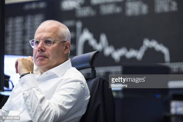 A trader monitors financial data as the DAX index curve shows stock information inside the Frankfurt Stock Exchange operated by Deutsche Boerse AG in...