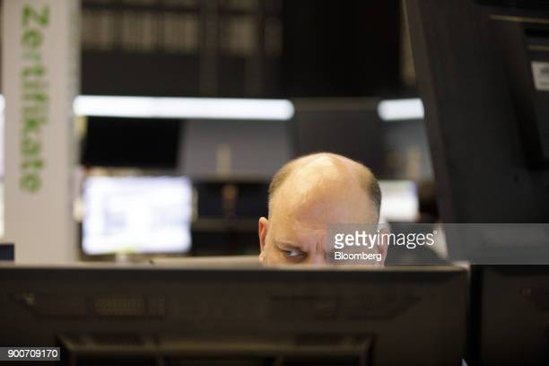 A trader monitors financial data as the second iteration of the Markets in Financial Instruments Directive comes into force at the Frankfurt Stock...