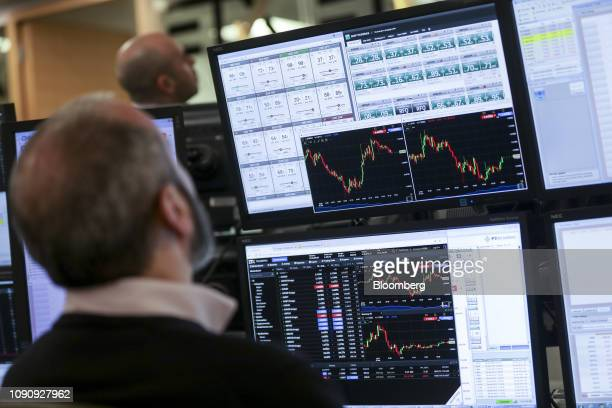 A trader monitors financial data on computer screens on the trading floor at ETX Capital a broker of contractsfordifference during UK parliamentary...