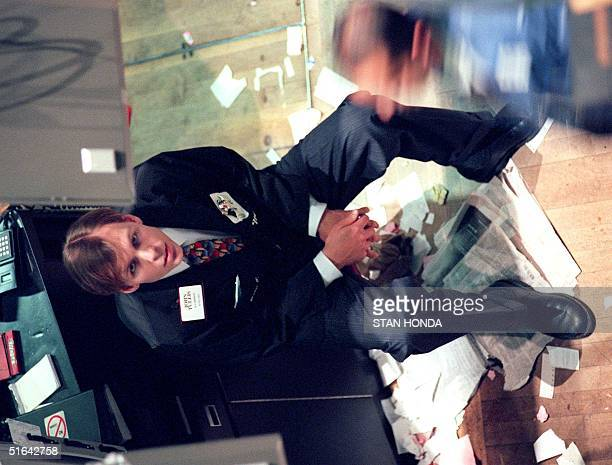 A trader on the floor of the New York Stock Exchange stares at a monitor after trading was halted as the Dow Jones Industrial Average closed down...