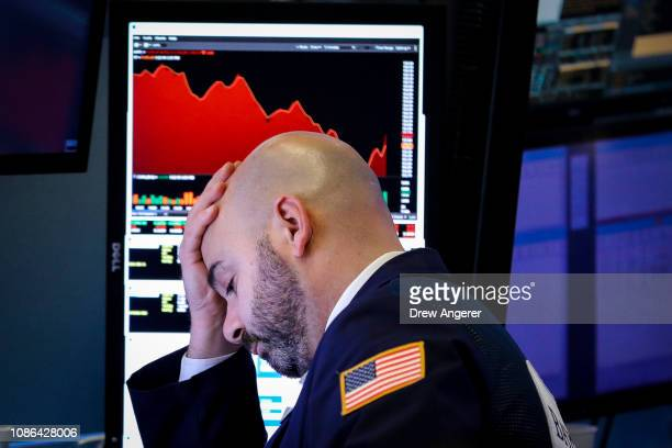 A trader pauses at his desk ahead of the closing bell on the floor of the New York Stock Exchange January 22 2019 in New York City Markets were down...