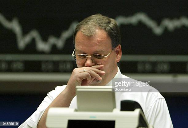 A trader pauses in front of the DAX Index board at the Frankfurt stock exchange Monday May 10 2004 Stocks sank in Europe and tumbled in Asia as a...