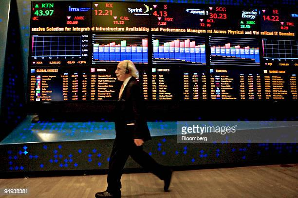 Trader Peter Tuchman walks by an eletronic stock board on the floor of the New York Stock Exchange in New York US on Monday April 27 2009 US stocks...