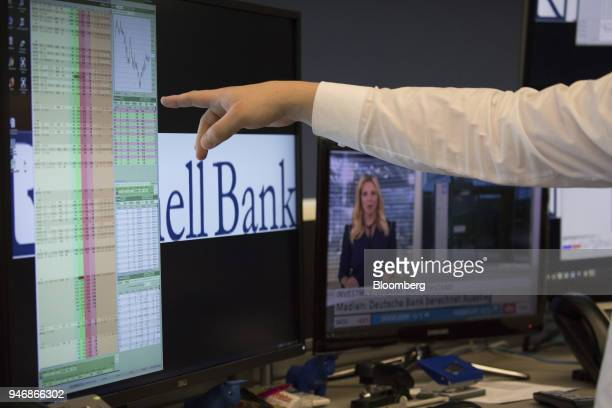 A trader points at financial data on a computer screen inside the Frankfurt Stock Exchange operated by Deutsche Boerse AG in Frankfurt Germany on...