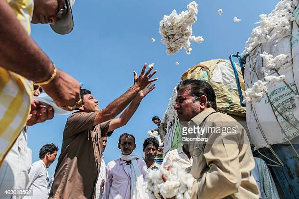 A trader reaches to catch a bundle of cotton for inspection during an auction at a local market in Yavatmal Maharashtra India on Wednesday Feb 4 2015...