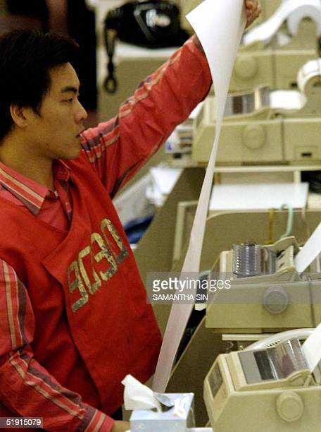 A trader reads a copy of index figures at the end of afternoon trading session at the Hong Kong Stock Exchange 05 January 2005 Hong Kong share prices...