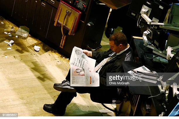 A trader reads a newspaper on the floor of the New York Stock Exchange on October 14 2009 in New York New York The Dow Jones industrial average past...