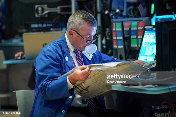 A trader reads the newspaper and blows a bubble on the floor of the New York Stock Exchange at the opening bell on August 19 2019 in New York City...