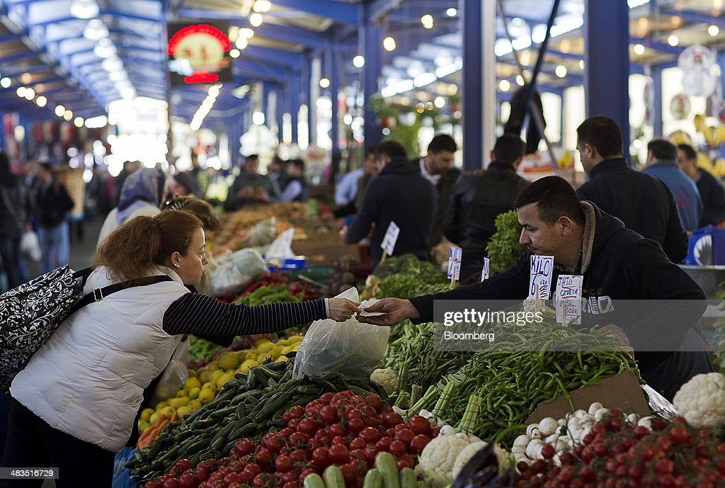 A trader, right, collects lira banknotes in payment for vegetables purchased at a stall in the Yesilkoy street market in Istanbul, Turkey, on Wednesday, April 9, 2014. Turkish central bank Governor Erdem Basci indicated to analysts in London on April 3 that he planned to keep monetary policy tight to control inflation. Photographer: Kerim Okten/Bloomberg via Getty Images