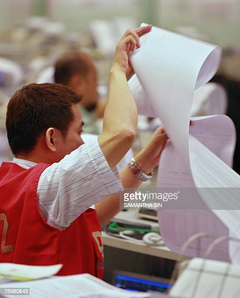 A trader rolls up stock reports as the Hong Kong Stock exchange closes in Hong Kong 06 August 2007 The Hang Seng Index closed down 60171 points or...