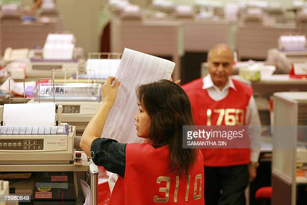 Trader rolls up stock reports as the Hong Kong Stock exchange closes, in Hong Kong, 06 August 2007. The Hang Seng Index closed down 601.71 points or...