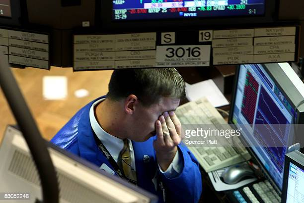 A trader rubs his face as he works on the floor of the New York Stock Exchange September 29 2008 in New York City US stocks took a nosedive in...