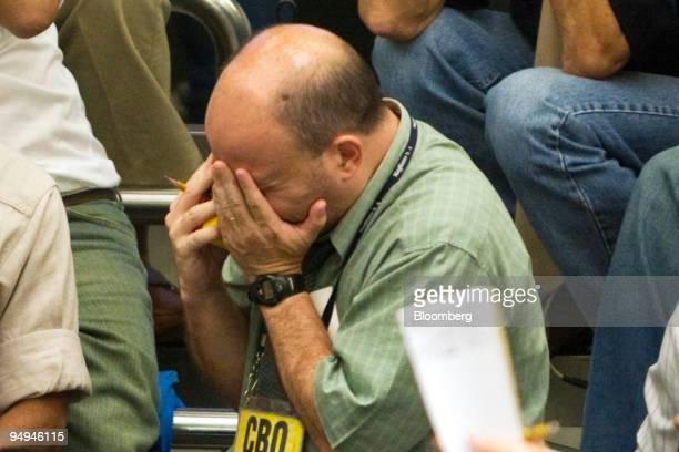 A trader rubs his face while working on the floor at the Bolsa de Mercadorias e Futuros or Brazilian Mercantile and Futures Exchange in Sao Paulo...