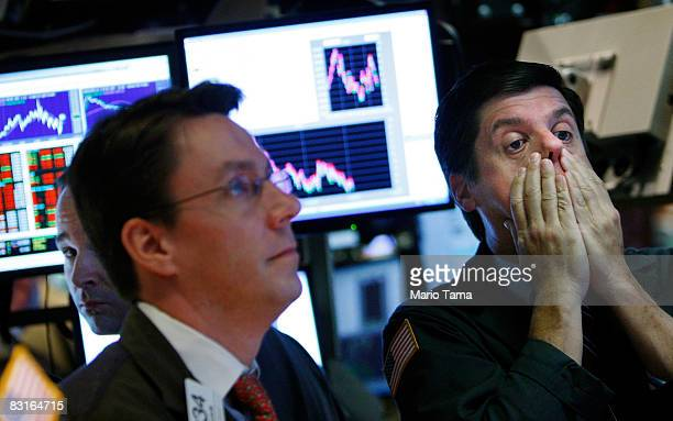 A trader rubs his face while working on the floor of the New York Stock Exchange October 7 2008 in New York City Despite a government debt buyout...