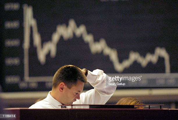 A trader rubs his head July 25 2002 at the Frankfurt stock exchange in Germany as the graph behind shows the German DAX stock index The DAX reached...