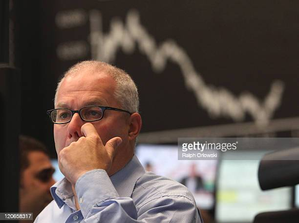 Trader rubs his nose in front of a graph showing the day's performance of the DAX index at the Frankfurt Stock Exchange on the first day following...