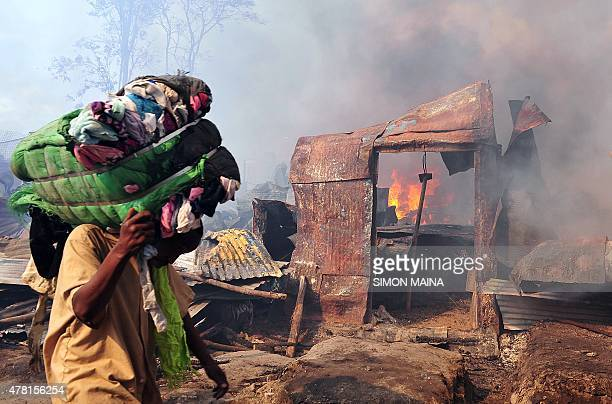 A trader salvages a bundle of clothing after a fire burned through part of Gikomba market East Africa's largest second hand clothing market in...