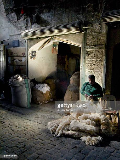 Trader sifts through wool during the early morning hours in the Aleppo souq, Syria.