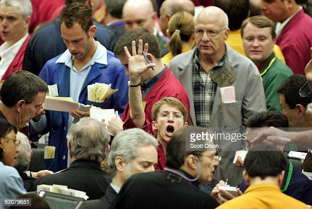 A trader signals an offer in the Cattle Futures pit at the Chicago Mercantile Exchange March 14 2006 in Chicago Illinois The pit saw a brisk opening...