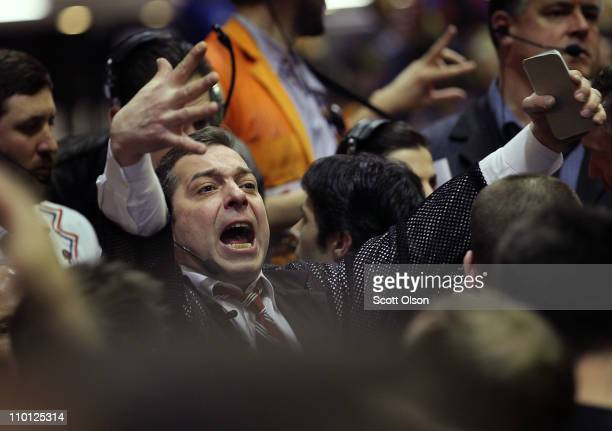 Trader signals an offer in the corn options pit at the CME Group March 15, 2011 in Chicago, Illinois. U.S. Stock and commodity prices tumbled today...