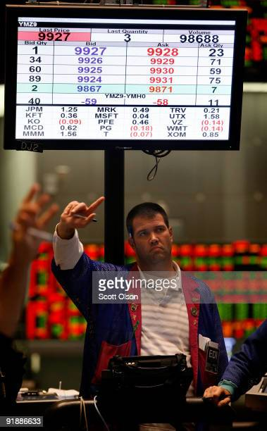 A trader signals an offer in the Dow Jones Industrial Average stock index futures pit on the CME Group trading floor October 14 2009 in Chicago...