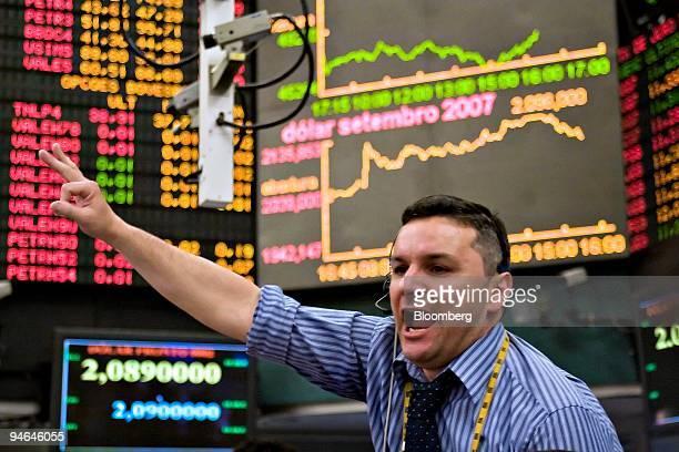 A trader signals orders at the Brazilian Bolsa de Mercadorias e Futuros the Brazilian Mercantile and Futures Exchange or BMF in Sao Paulo Brazil...