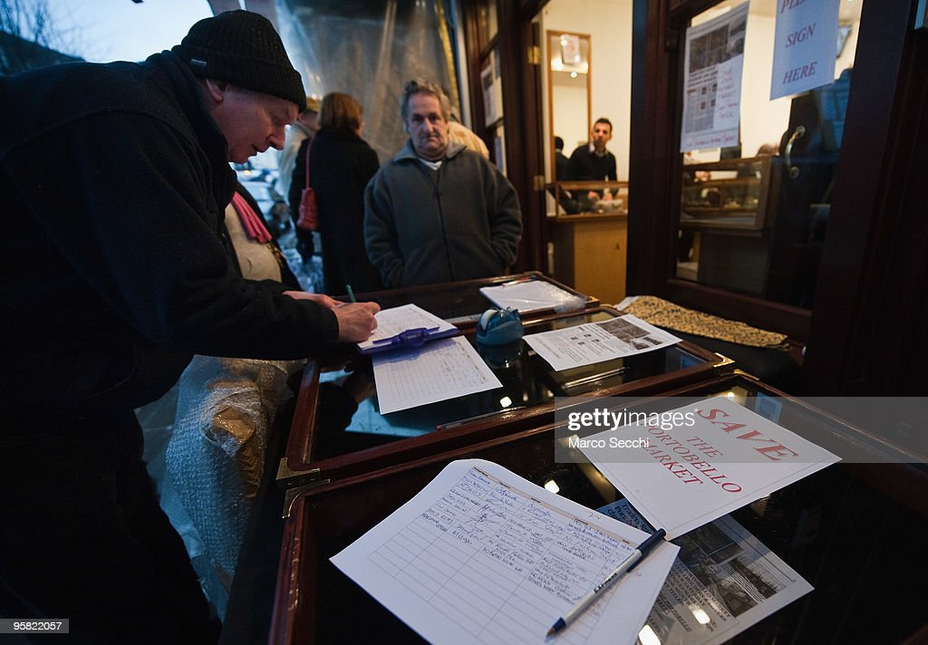 A trader signs a petition to save Portobello Market on January 16, 2010 in London, England. Portobello traders fear for the Market's future after Lipka's Antiques Arcade, where more than 150 traders had their stalls, was redeveloped to accommodate a large High street chain store.