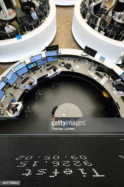 A trader sit at his desk under the day's performance board that shows a dive in the value of the DAX index of companies at the Frankfurt Stock...