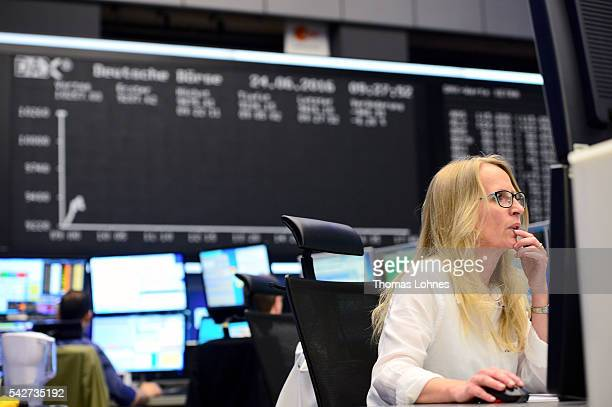 Trader sits at her desk under the day's performance board that shows a dive in the value of the DAX index of companies at the Frankfurt Stock...