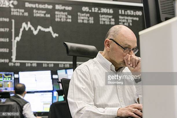 A trader sits at his desk and monitors financial data as the movements of the DAX Index curve are displayed on a screen inside the Frankfurt Stock...