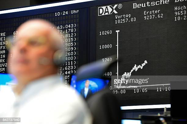 Trader sits at his desk under the day's performance board that shows a dive in the value of the DAX index of companies at the Frankfurt Stock...