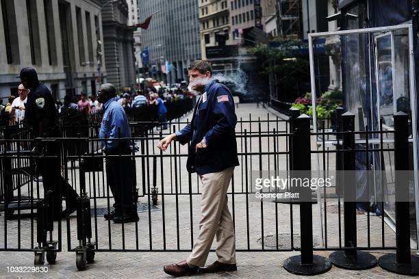 A trader smokes along Wall Street on the ten year anniversary of the US financial crisis September 14 2018 in New York City The September 15th 2008...