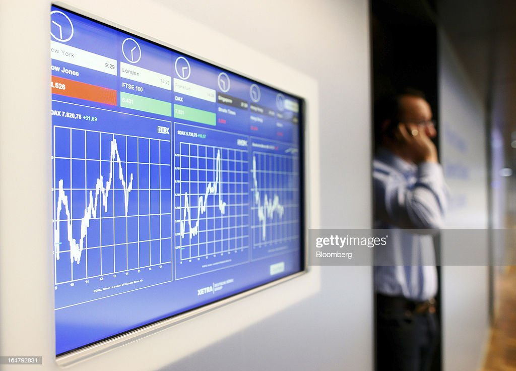 A trader speaks on a mobile handset near a monitor displaying index curves for the DAX, left, MDAX, centre, and Deutsche Borse AG at the Frankfurt Stock Exchange in Frankfurt, Germany, on Thursday, March 28, 2013. Cyprus's lenders had been closed since March 16, when the European Union presented a proposal to force losses on all depositors in exchange for a 10 billion-euro bailout. Photographer: Ralph Orlowski/Bloomberg via Getty Images