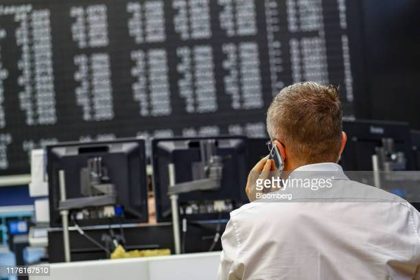 Trader speaks on a mobile phone inside the Frankfurt Stock Exchange, operated by Deutsche Boerse AG, in Frankfurt, Germany, on Wednesday, Oct. 16,...