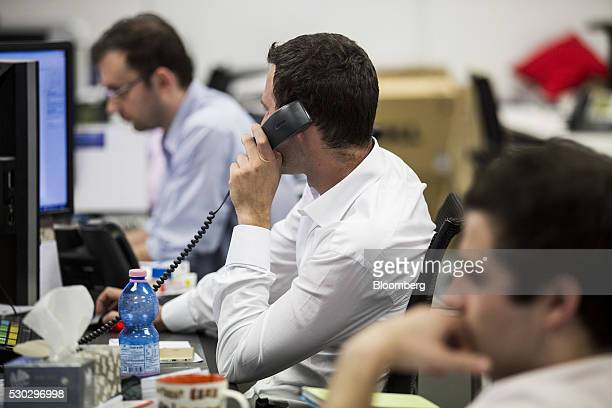 A trader speaks on a telephone at the BFAM Partners Ltd office in Hong Kong China on Monday May 9 2016 Benjamin Fuchs founder of BFAM Partners has...