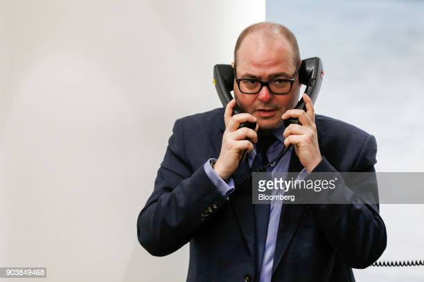 A trader speaks on fixed line telephones on the trading floor of the open outcry pit at the London Metal Exchange Ltd in London UK on Thursday Jan 11...