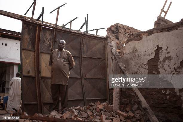 A trader stands in the rubble of his shop destroyed in a blaze which damaged 47 shops on January 17 in Bangui's predominantly Muslim PK5 quarter on...