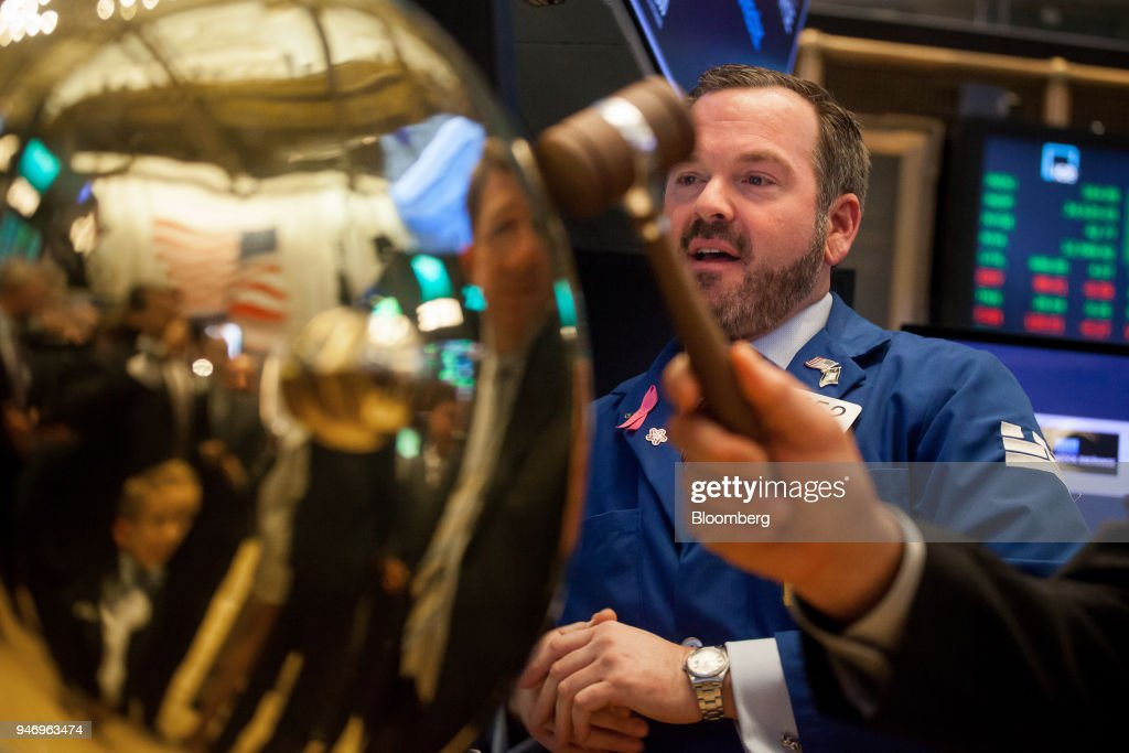 A trader stands next to the ringing of a ceremonial bell celebrating the January 2018 initial public offering (IPO) of Nine Energy Service Inc. on the floor of the New York Stock Exchange (NYSE) in New York, U.S., on Monday, April 16, 2018. U.S. stocks rallied and Treasuries slid as geopolitical tensions eased and investors turned their attention to corporate results. Photographer: Michael Nagle/Bloomberg via Getty Images